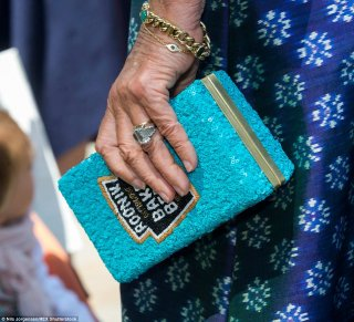 Confident: The Duchess shows off a quirky bag-shaped like a will of beans along with her gemstone - its considered really worth £100,000